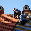 Two roofers install clay roofing tiles, a green roofing material. (Photo: majorosl/istockphoto.com)