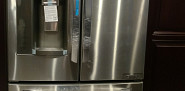 New LG fridge next to our kitchen cabinet