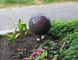 A DIY mosaic garden ornament gleams with pieces of broken mirror. (the1pony/flickr creative commons)