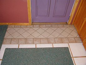 This ceramic tile rug right in front of the door is in lieu of ripping out all of the tile. Photo and tile repair by Kevin Stevens.
