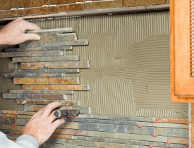 Photo of someone installing a tile backsplash by BanksPhotos/istockphoto.com