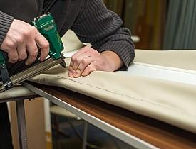 Photo of an upholsterer using an upholstery gun by AzmanL/istockphoto.com.