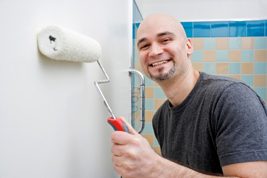 Photo of a DIY-er painting a bathroom wall by michellegibson/istockphoto.com.