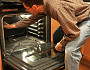 Photo of a man cleaning an oven by akit/istockphoto.com.