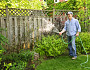 Man watering garden near tall fence