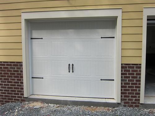Carriage doors versus roll up doors networx for Swing out garage doors price